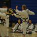 An adult woman black belt breaking a board using martial arts
