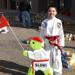 A taekwondo kid smiling in front of a martial arts school for kids