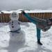 Martial arts girl doing a kick with a snowman in Colorado