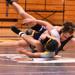 Two wrestlers wrestling.