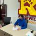 Minneapolis Roosevelt High School in South Minneapolis. Devon sitting in front of the big R logo at the school, signing his letter of intent to play football and attend Itasca Community College in the fall of 2021