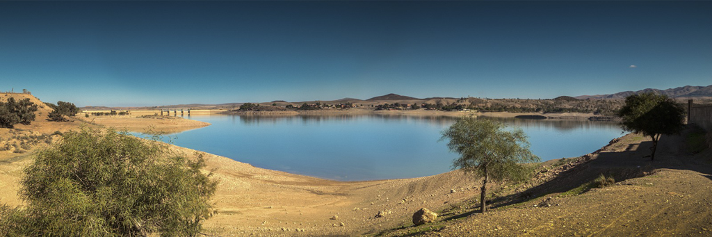 Lake surrounded by a few trees and mountains in Marrakech, Morocco