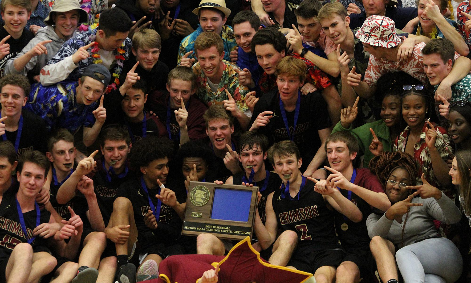 Maple Grove poses with its student section after clinching the Class 4A, Section 8 title Thursday night in St. Michael. The Crimson defeated Buffalo 77-64. Photo by Drew Herron, SportsEngine