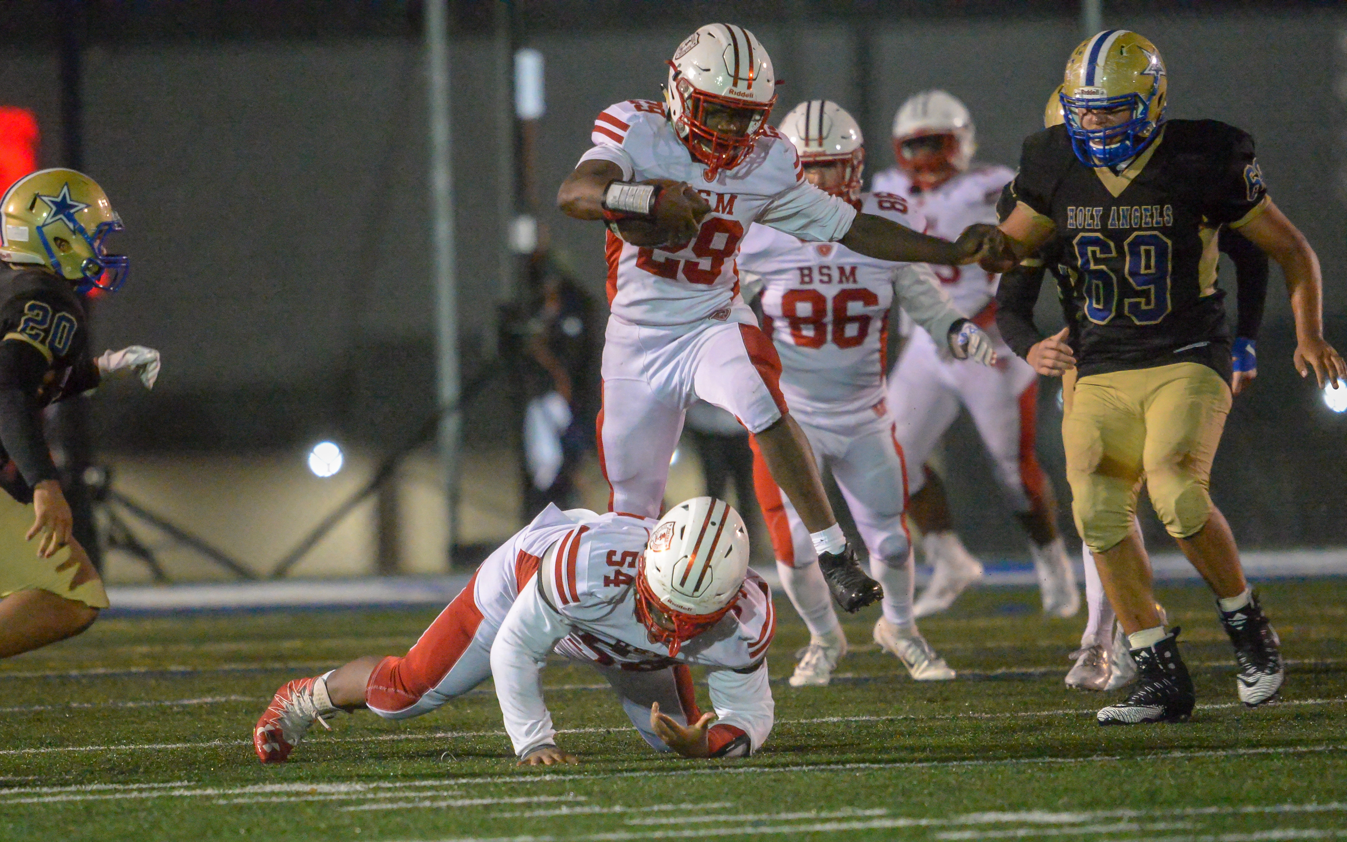 Benilde-St. Margaret's junior Isaiah Smith hurdles his teammate Elijah Brown in hopes of reaching the end zone in the third quarter. The Red Knights lost to the Stars 34-17 on a misty Friday night. Photo by Earl J. Ebensteiner, SportsEngine
