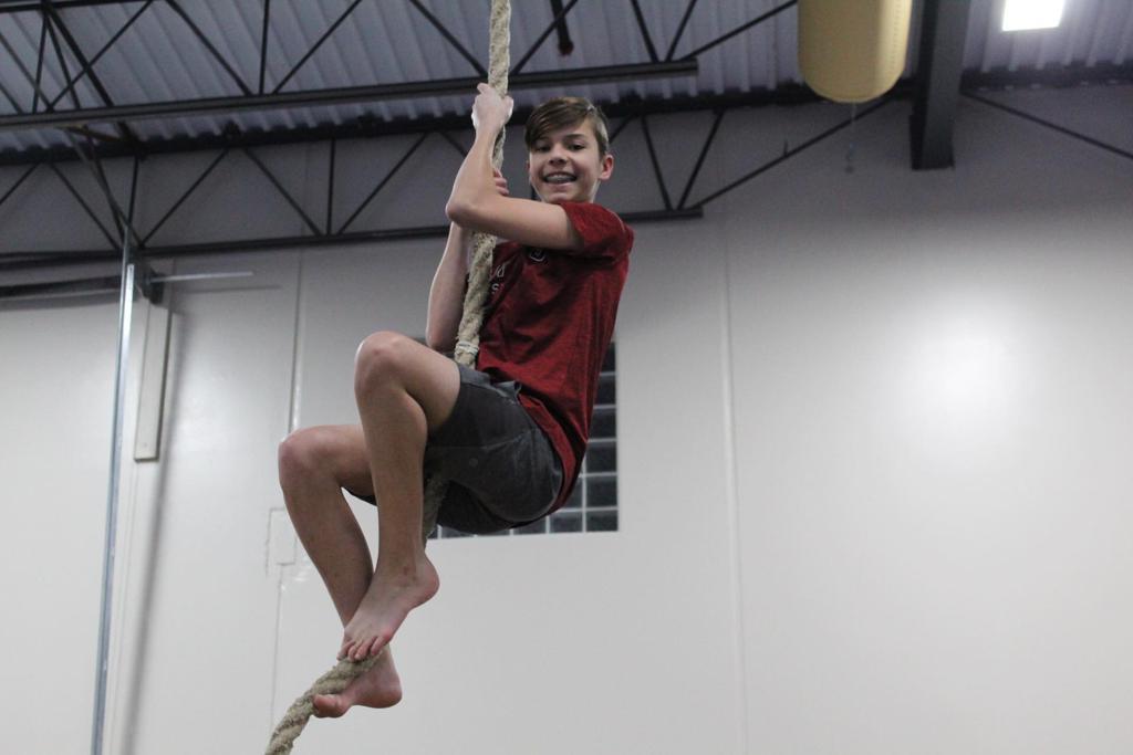 boy gymnast climbing rope