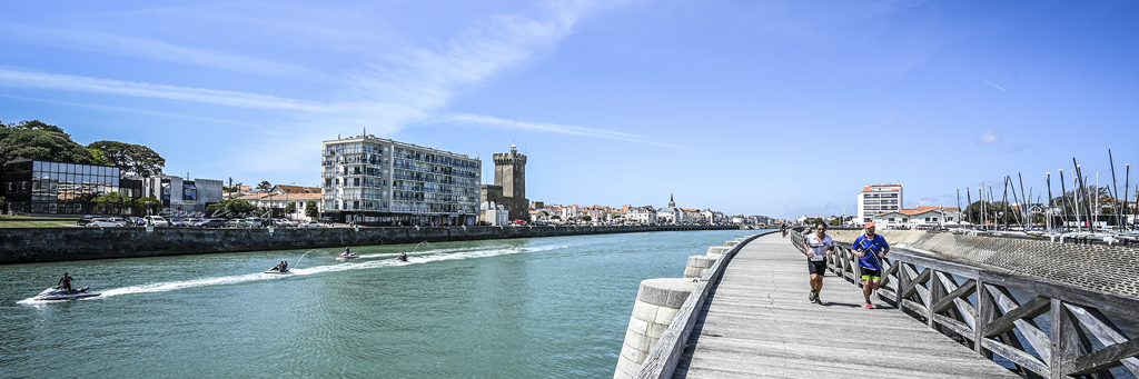 Athletes are running along the Tanchet lake on the famous promenade of Sables d'Olonne