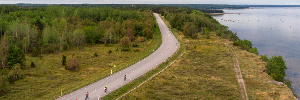 Bird's eye view of athletes biking along a street next to the sea and woods at IRONMAN Tallinn