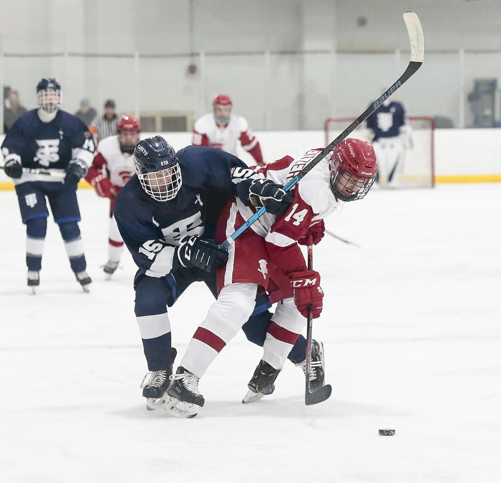 Benilde-St. Margaret's Nate Schweitzer (14) fights for possession with Jackson Hallum (15) at mid-ice. Schweitzer tallied two assists in the Red Knights' 3-2 loss to the Cadets at the St. Louis Park Rec Center. Photo by Cheryl A. Myers, SportsEngine