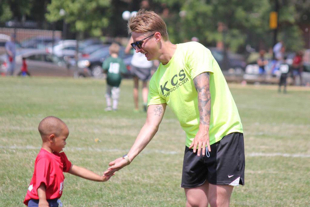 coach high fiving toddlers player