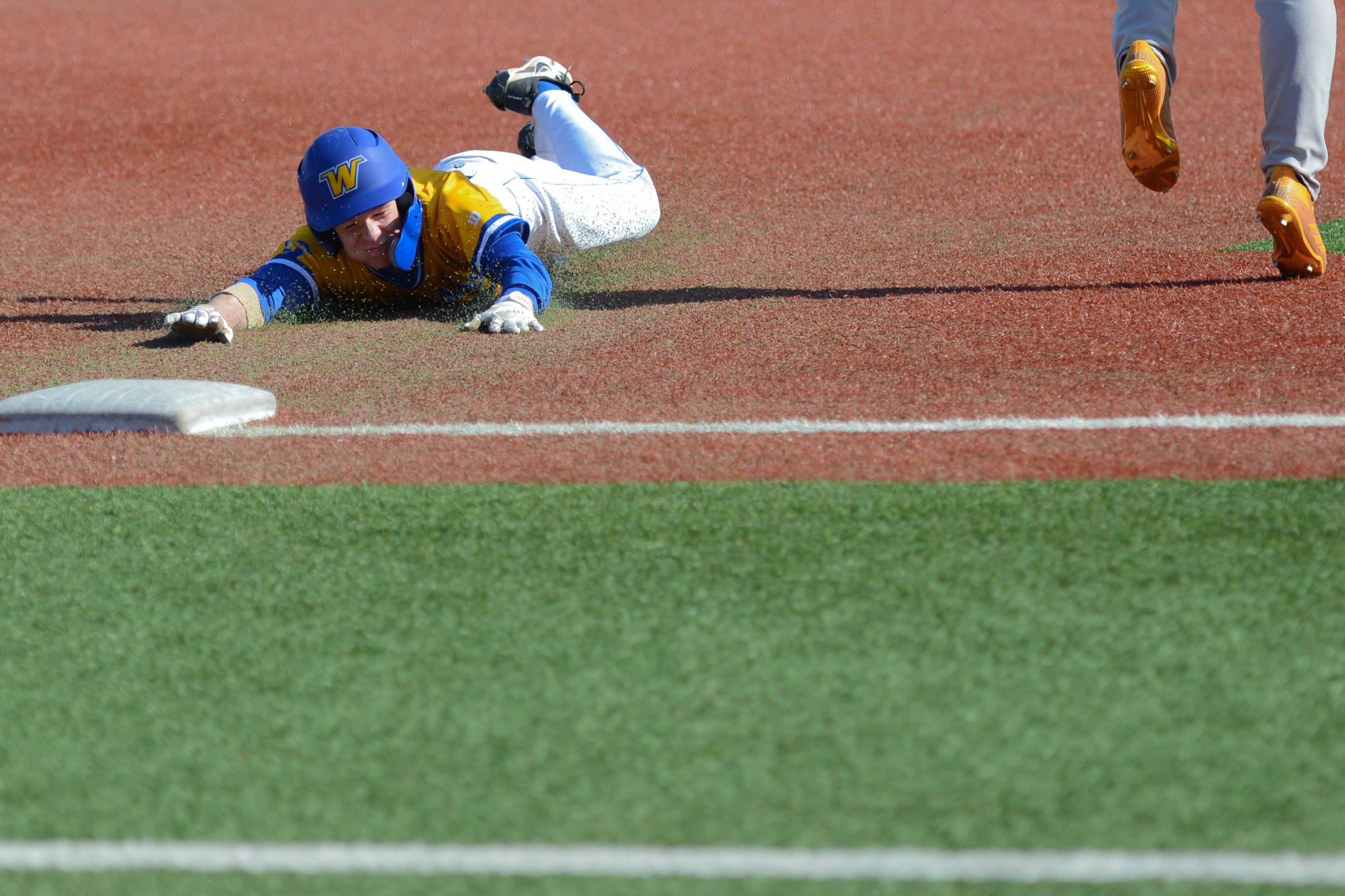 A Wayzata baserunner slides into third base against Totino-Grace during the Trojans' 7-4 loss to the Eagles Saturday. Photo by Carter Jones, SportsEngine