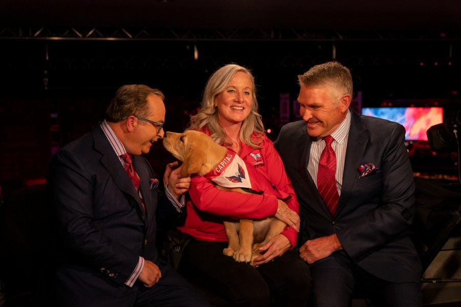 Captain and Deana Stone (center) mingle with Capitals' broadcasters. Stone has been Captain's puppy raiser from America's VetDogs. Photo courtesy of the Washington Capitals
