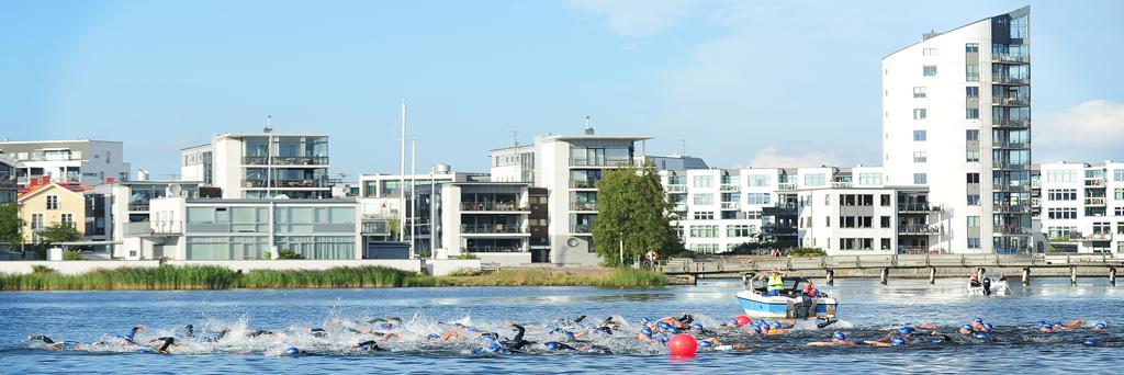 Athletes with blue swim caps are swimming at Kattrumpan beach at Kalmar Mini Tri next to houses on the shore