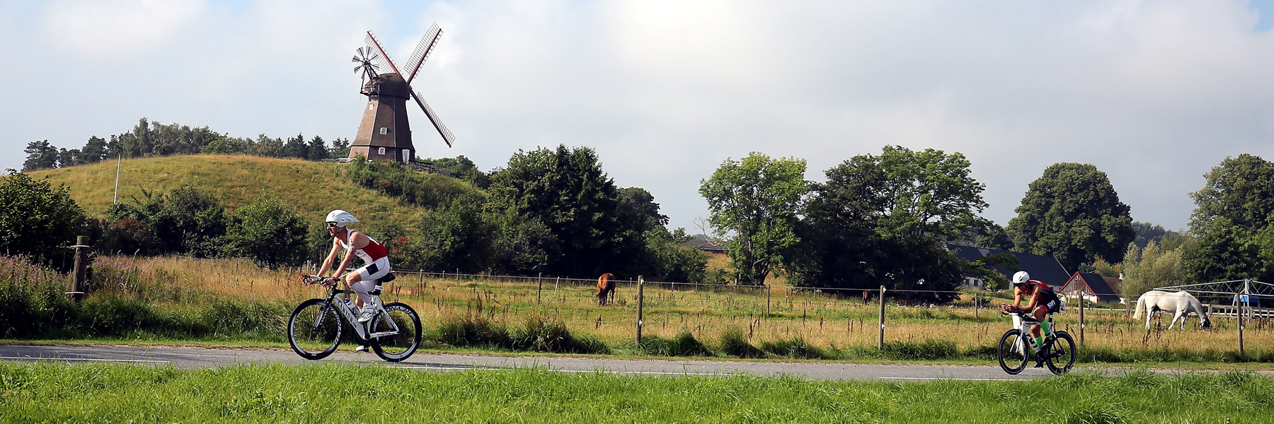 IRONMAN Copenhagen athletes biking through the green countryside next to horses and a windmill