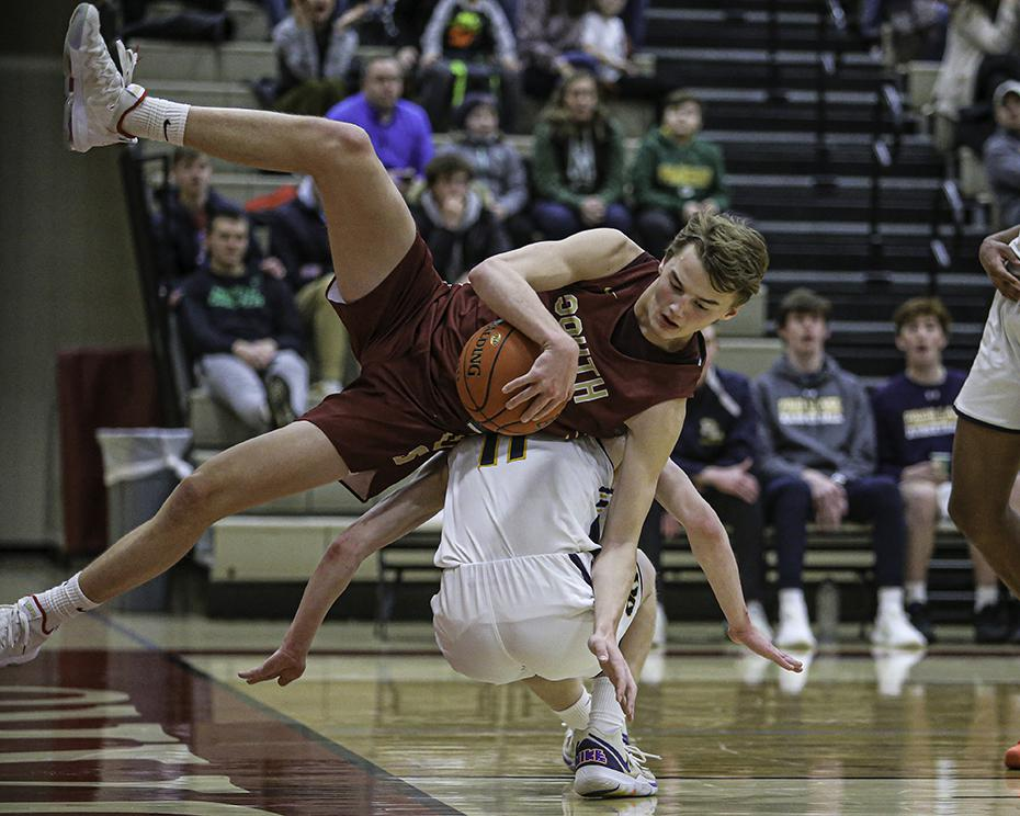 Lakeville South's Avery Mast had his feet cut out from under him by Prior Lake's Tommy Mestnik as he came down with a second-half rebound. Photo by Mark Hvidsten, SportsEngine