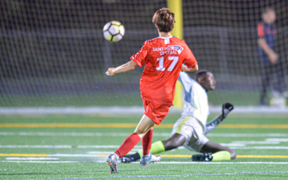 St. Paul Central's Thomas Bump enters the game late in the first half and beats St. Paul Como Park goalie Emmanuel Molinos Lopez, scoring the game-winner to keep the Minutemen undefeated in league play Tuesday. Photo by Earl J. Ebensteiner, SportsEngine