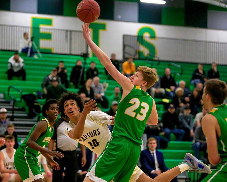 East Ridge sophomore Kendall Brown tried to scoop the ball under Edina defender Tommy Denn for a second-half basket. Brown scored a game-high 24 points. Photo by Mark Hvidsten, SportsEngine