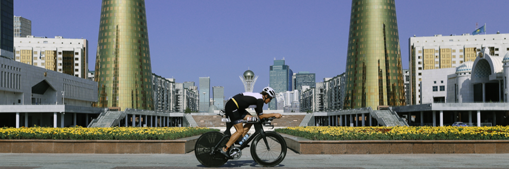 IRONMAN 70.3 Astana athlete biking through Nur-Sultan with both Golden Towers and Baiterek Tower in the background
