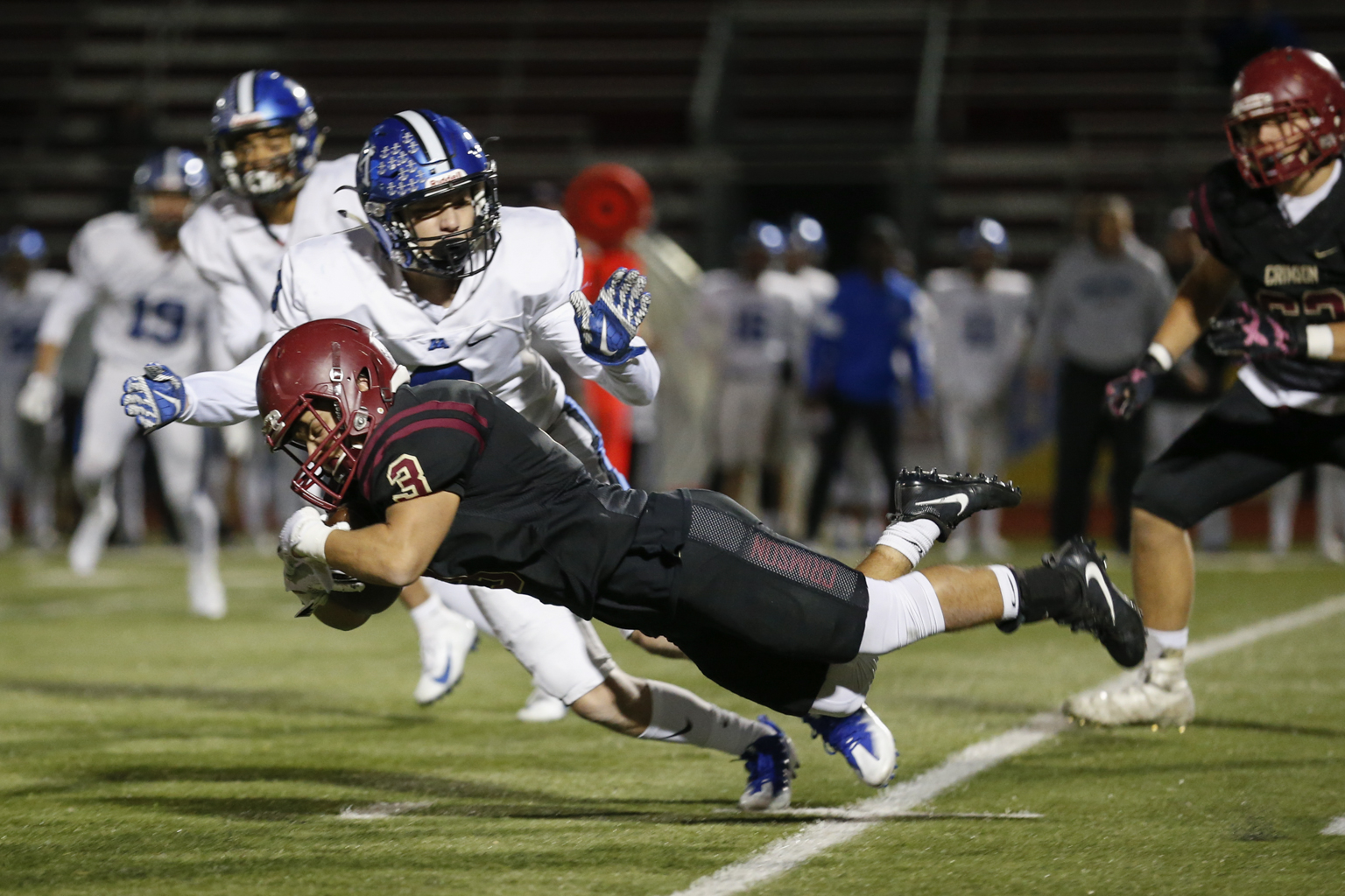 Maple Grove's Cooper Wegscheid (3) dives for extra yards at the end of a first quarter rush against Minnetonka. The Crimson defeated the Skippers 26-3 at Maple Grove High School. Photo by Jeff Lawler, SportsEngine