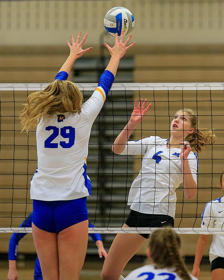 Minnetonka's Kali Engeman (4) had to react quickly after her kill attempt was blocked by Wayzata's Katelyn Empkey (29). Photo by Mark Hvidsten, SportsEngine