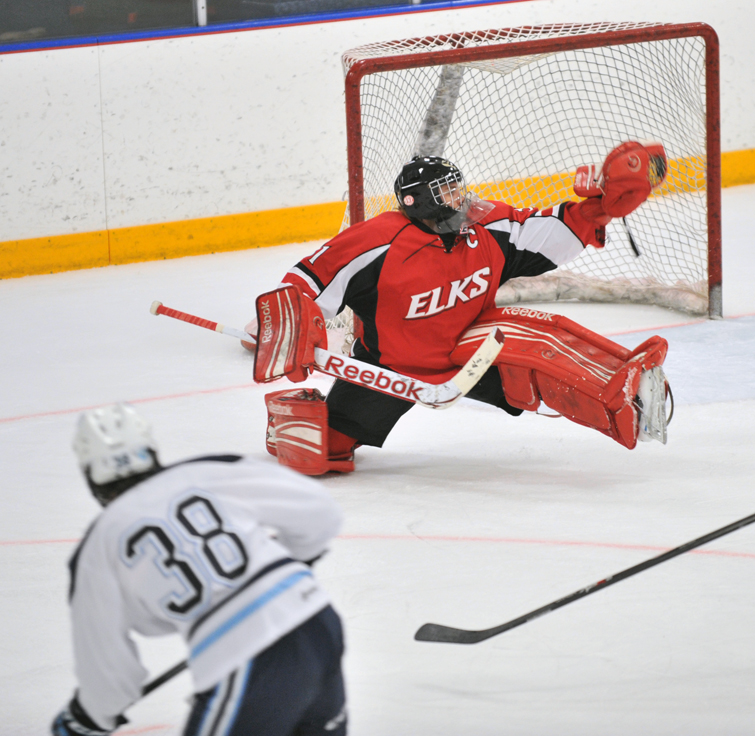Elk River goaltender Maclean Berglove makes a save on Blaine forward Dallas Gerads. Photo by Katherine Matthews