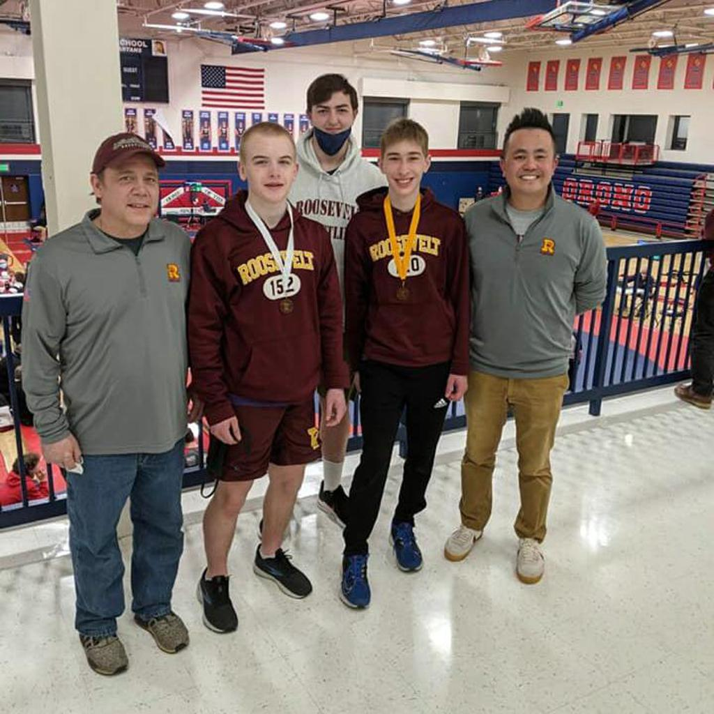 Teddy Wrestlers Isaak Larsen & Franklin Wohnoutka stand with their coaches proudly wearing their earned medals
