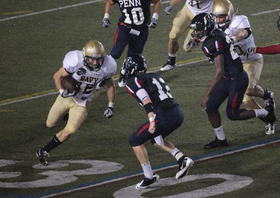 Nick Rush (12), a four-year member of Pennsylvania's sprint football team, sets to tackle at Navy ball carrier. | University of Pennsylvania