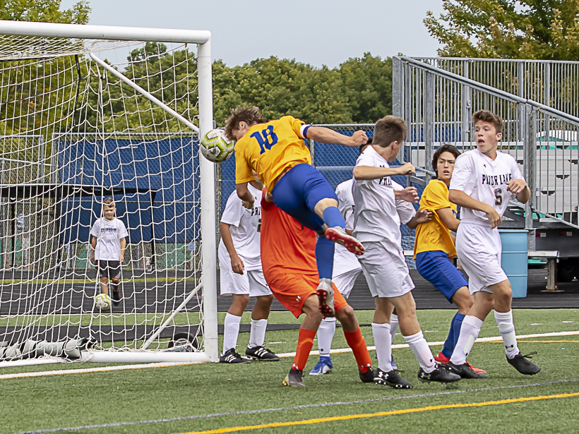 Wayzata senior midfielder Ben Luedtke scores on a header to put the Trojans up 1-0 against Prior Lake at Wayzata High School on Saturday. The Trojans defeated the Lakers 2-1. Photo by Gary Mukai, SportsEngine