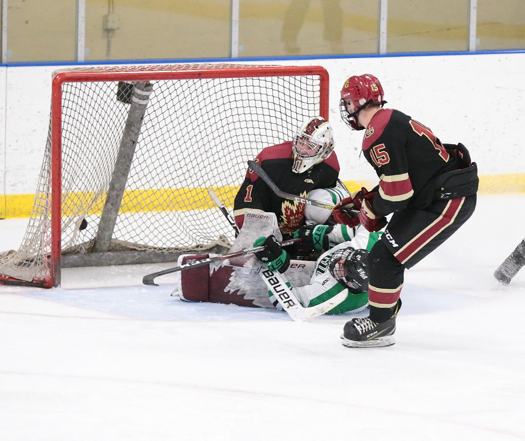 The Pioneers' Charlie Strobel slides through the crease as his second goal hits the back of the net.  Strobel's two goals helped Hill-Murray to a 4-1 win over Maple Grove. Photo by Cheryl A. Myers, SportsEngine