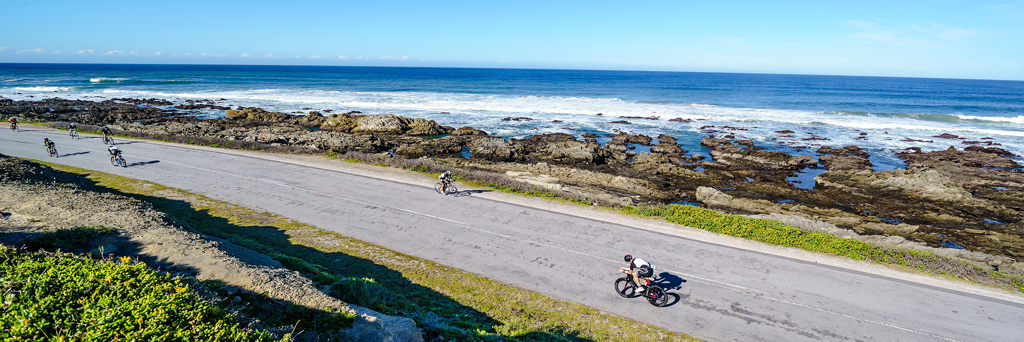Athletes biking on the rugged coastline next to the turquoise sea and foaming waves