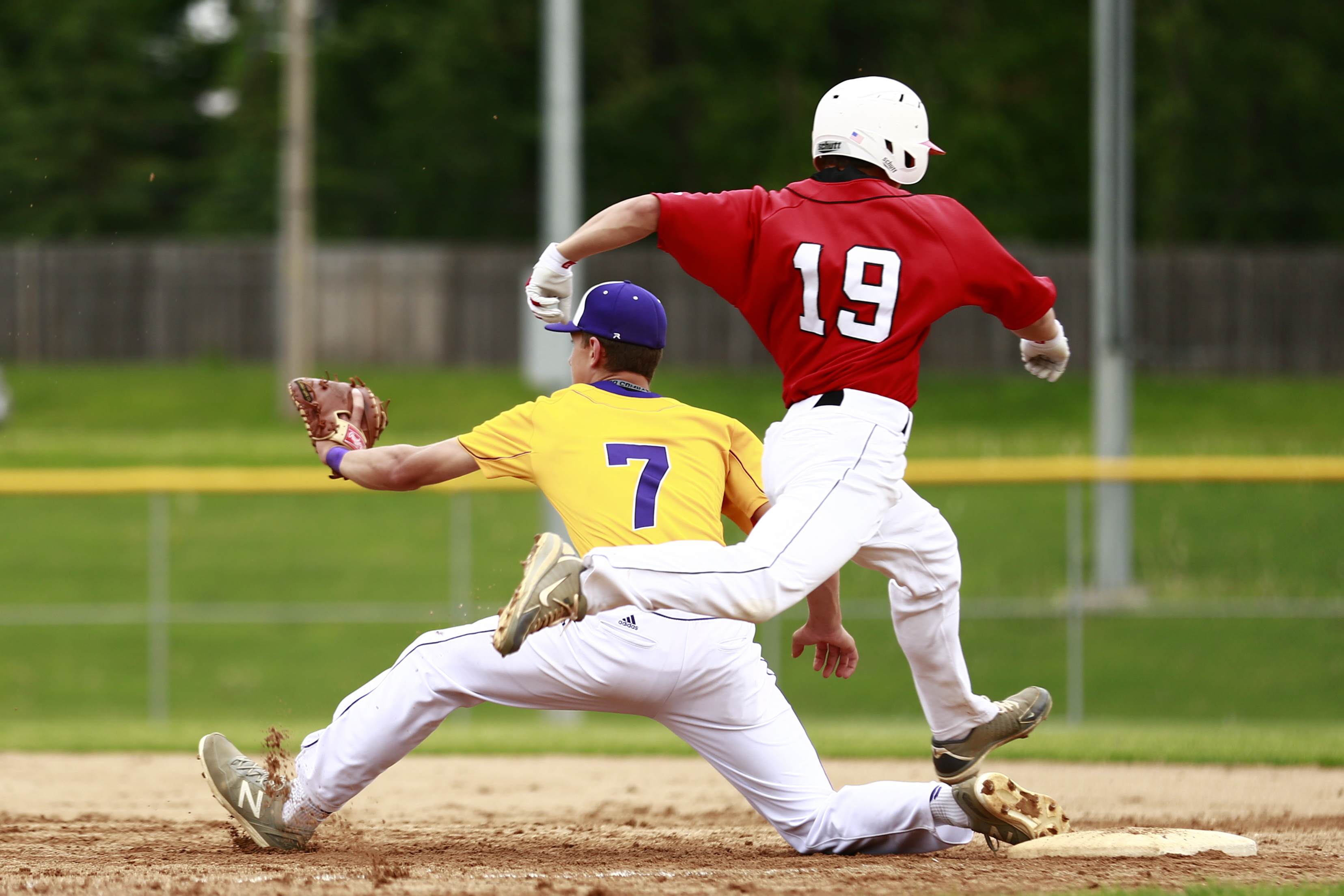 Spenser Larson (19) of Eden Prairie makes it safely to first base in a very close play, avoiding getting tagged out by Cole Peters (7). Photo by Chris Juhn