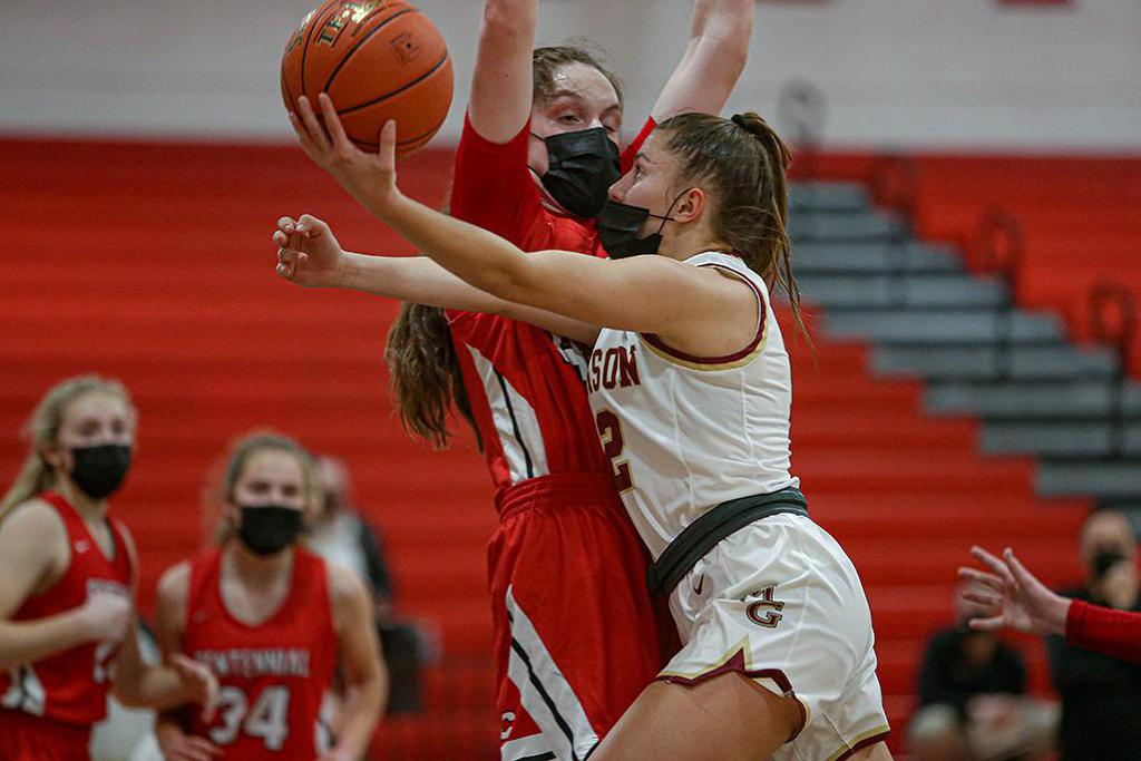 Maple Grove senior Kylie Baranick (12) took the ball to the basket against Centennial's Jenna Guyer in the first half. Baranick led the Crimson with 14 points. Photo by Mark Hvidsten, SportsEngine