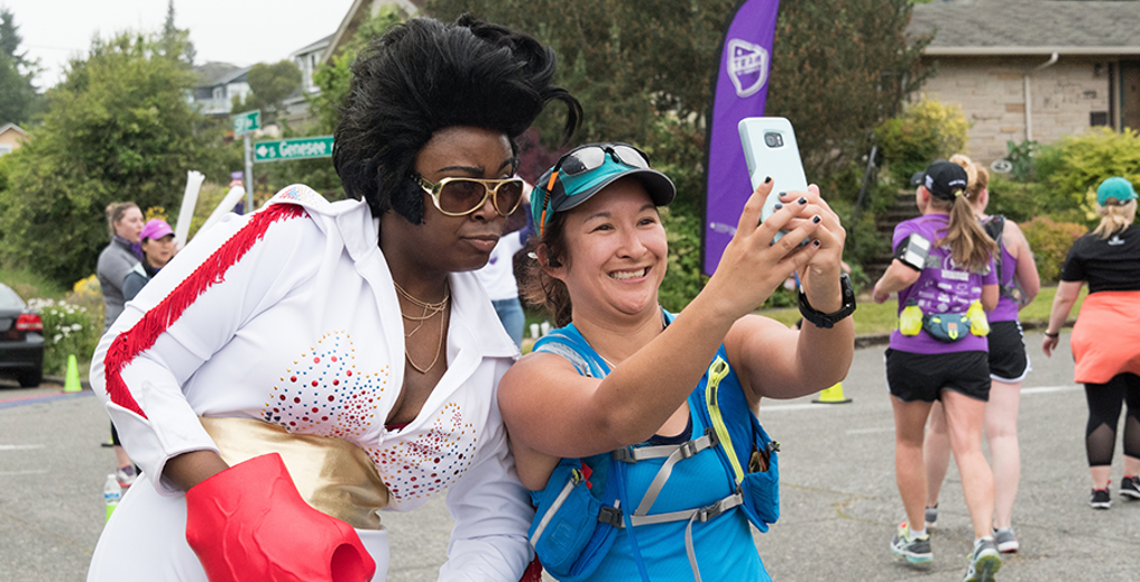 a woman taking a selfie with an elvis impersonator runner