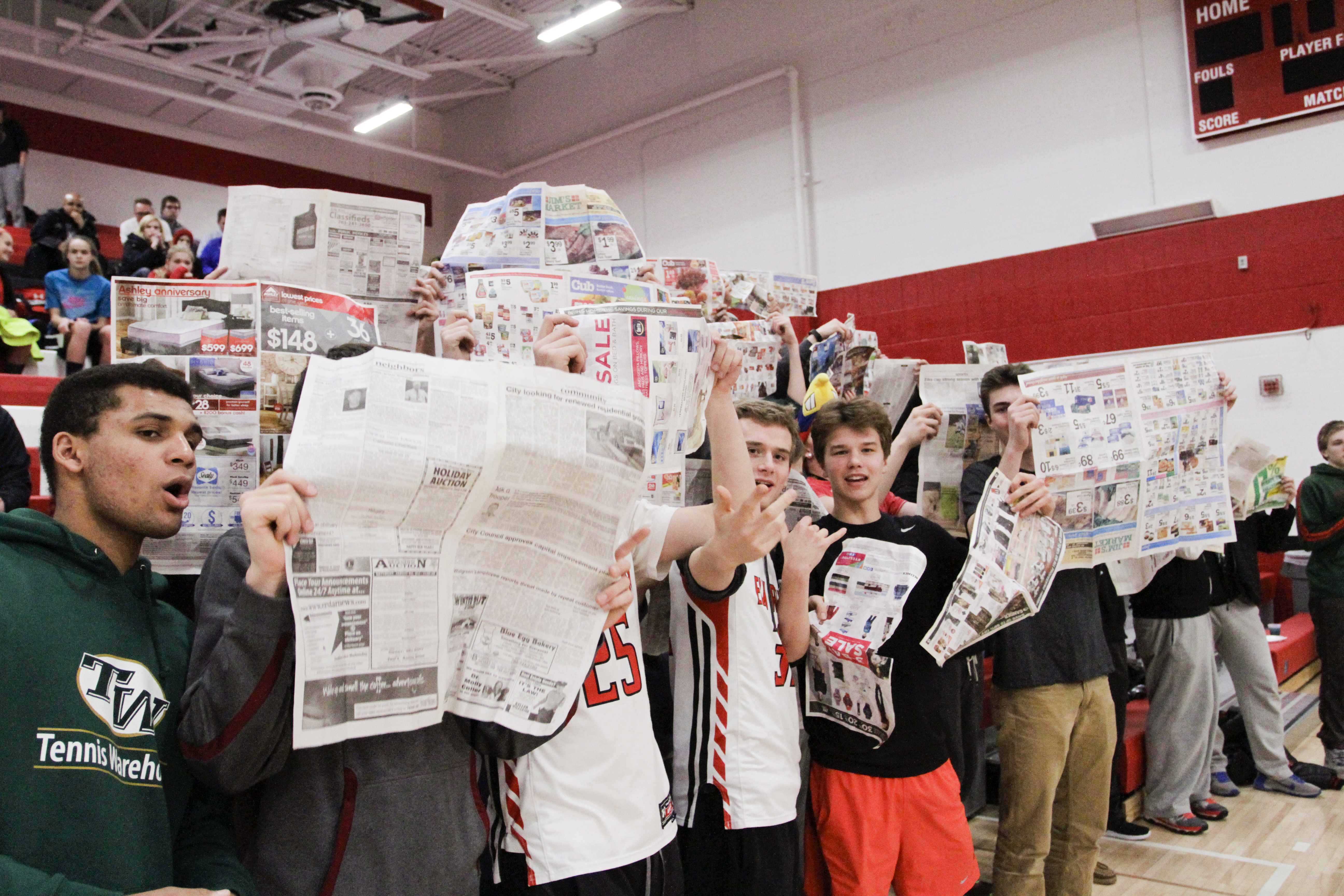 Elk River students hold newspapers up during the introduction of the opposing teams players. Photo by Chris Juhn