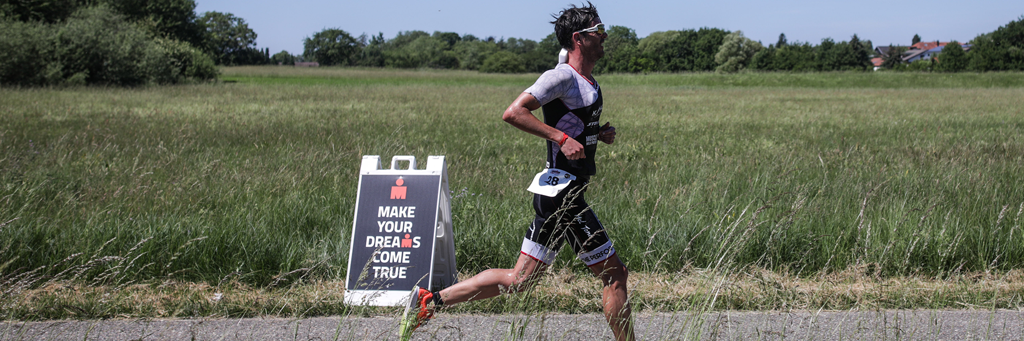 "IRONMAN 70.3 Kraichgau athlete running next to a field and a sign that says ""Make your dreams come true"""
