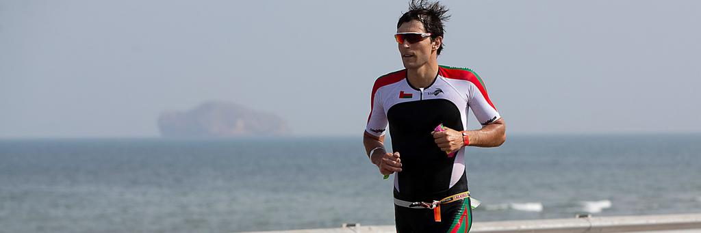 A single IRONMAN 70.3 Oman athlete running along the shore of the Sea of Oman