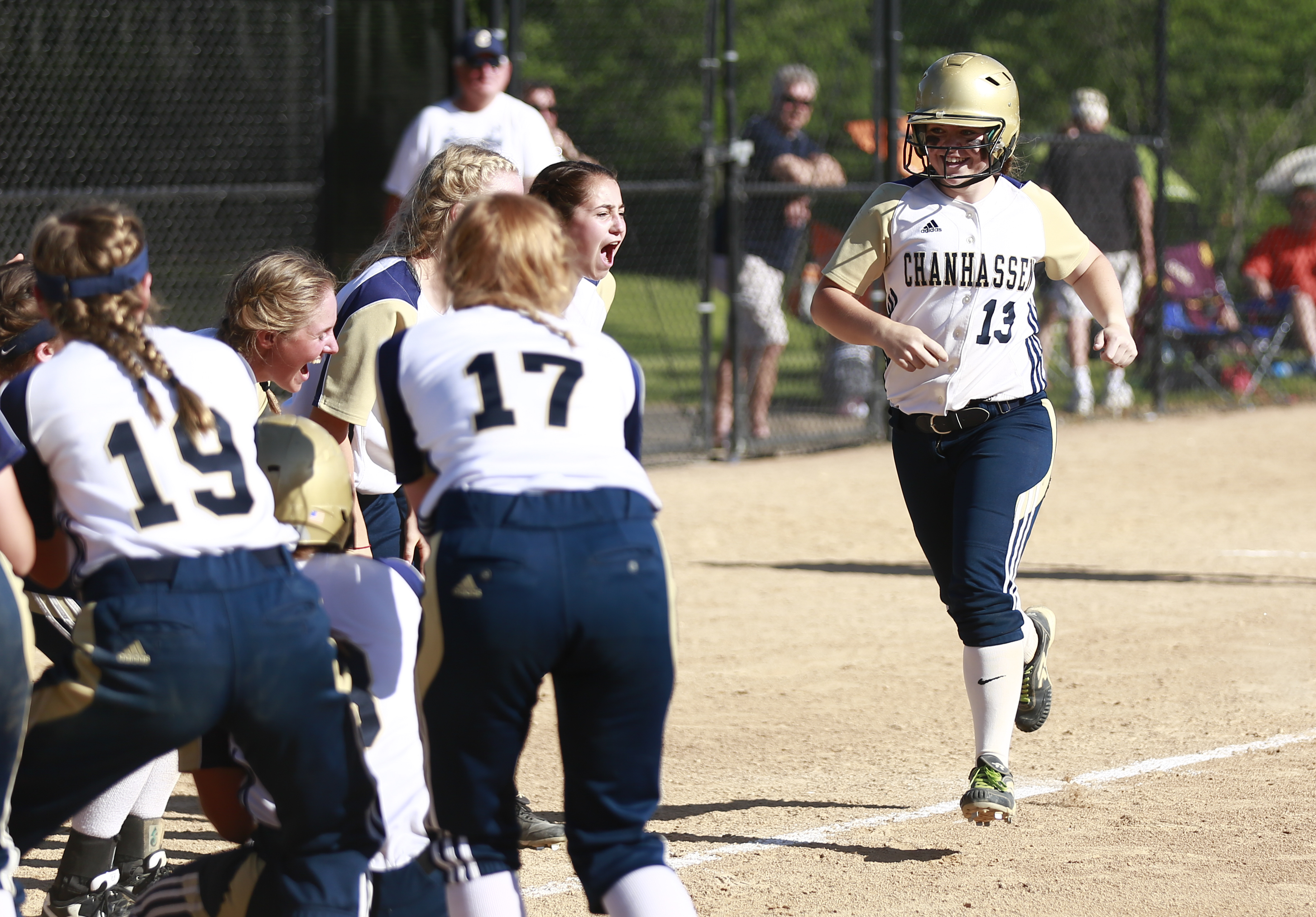 The Chanhassen Storm's Marybeth Olson (13) is cheered in by her teammates after hitting a two-run home run in the third inning of the Class 4A, Section . The Storm secured 6-3 victory over the Eagles, sending them to the state tournament. Photo by Chris J