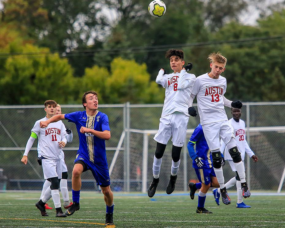 Holy Angels' Carter Hermanson (22) fielded the ball after Austin's Andres Garcia (8) and Lucas Evanson (13) deflected a goal kick. Hermanson's goal with 18 minutes to play gave Holy Angels a 1-0 victory. Photo by Mark Hvidsten, SportsEngine