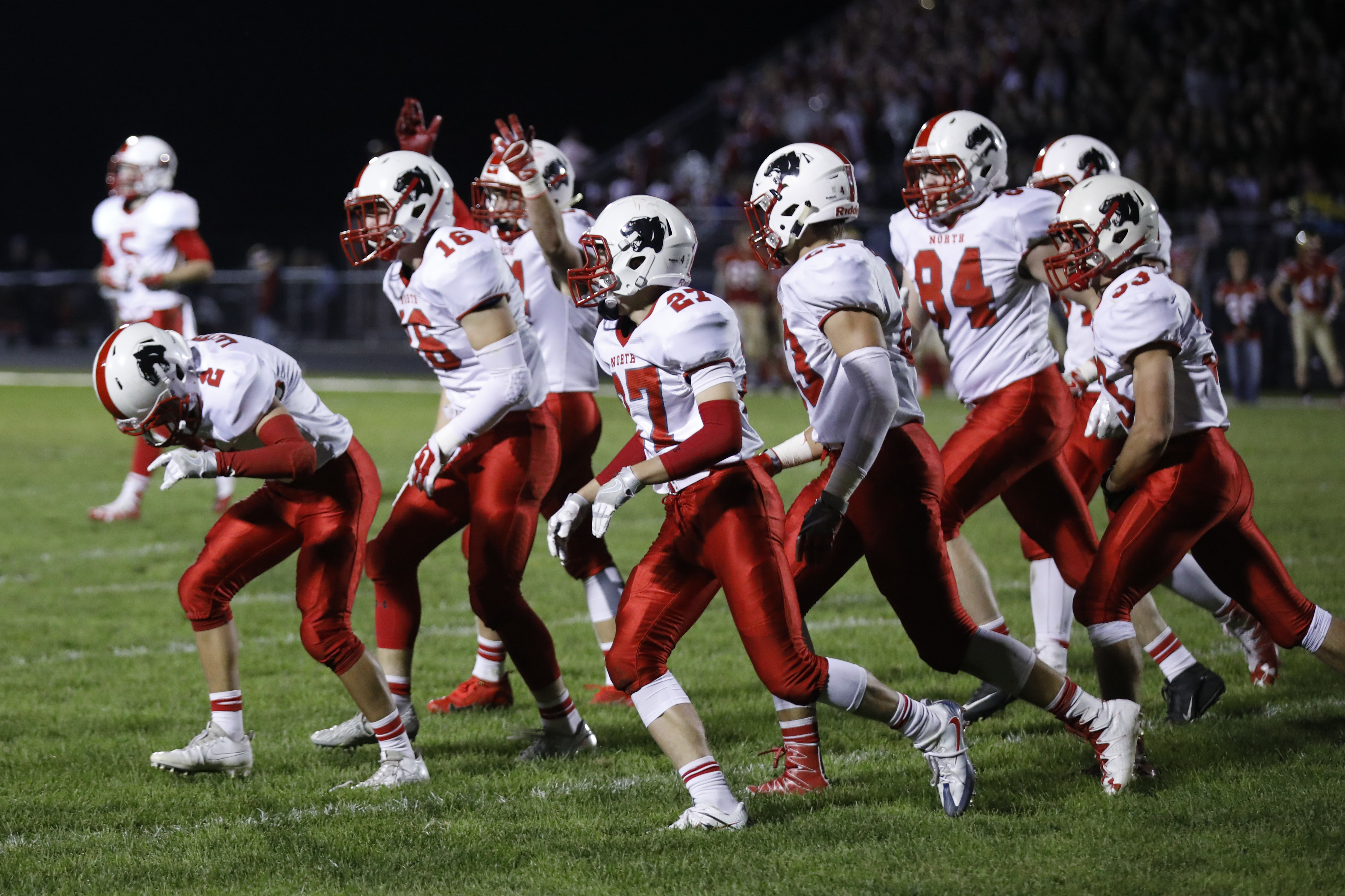 Lakeville North players celebrate on the field after Braden Walsh (16) intercepted a ball thrown by the Cougars quarterback. The Panthers defeated the Cougars 35-0 away. Photo by Chris Juhn