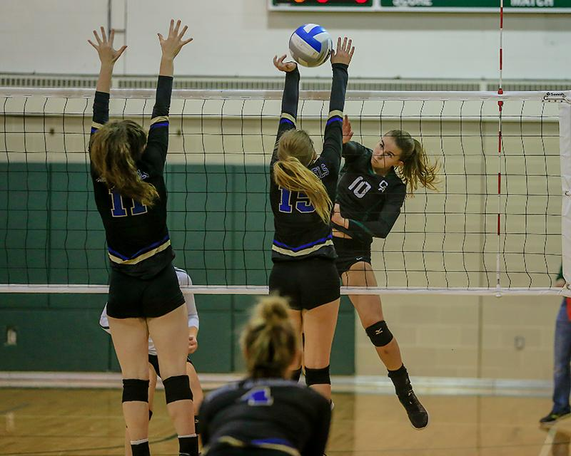 Beacons middle hitter Sarah McTaggart (10) scored with this shot past Stars defenders Rachel Erazmus (15) and Julie Mitchell. Photo by Mark Hvidsten, SportsEngine