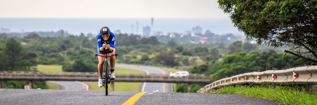 A single IRONMAN 70.3 South Africa athlete on his bike taking on the rolling hills towards the city in Buffalo City, East London