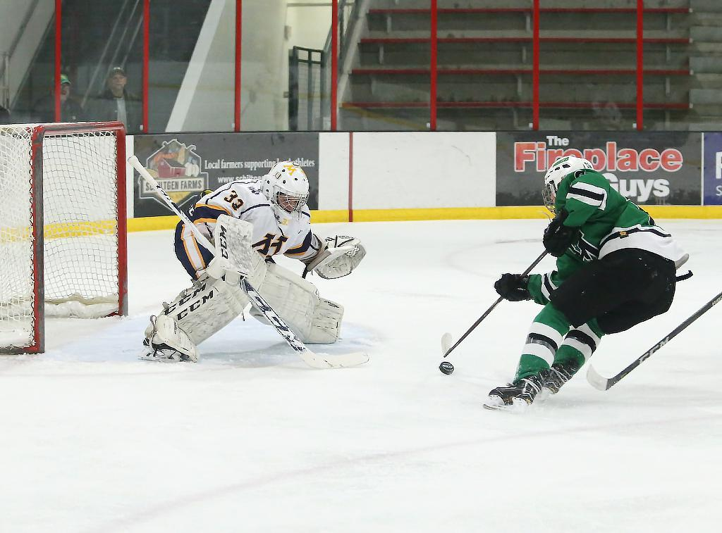 The Pioneer's Katie Kaufman picks up the bouncing pick and slides it past junior goaltender Lauren Hamme. Kaufman tallied a goal and two assists helping Hill-Murray cruise past Mahtomedi by a score of 5-1. Photo by Cheryl Myers, SportsEngine