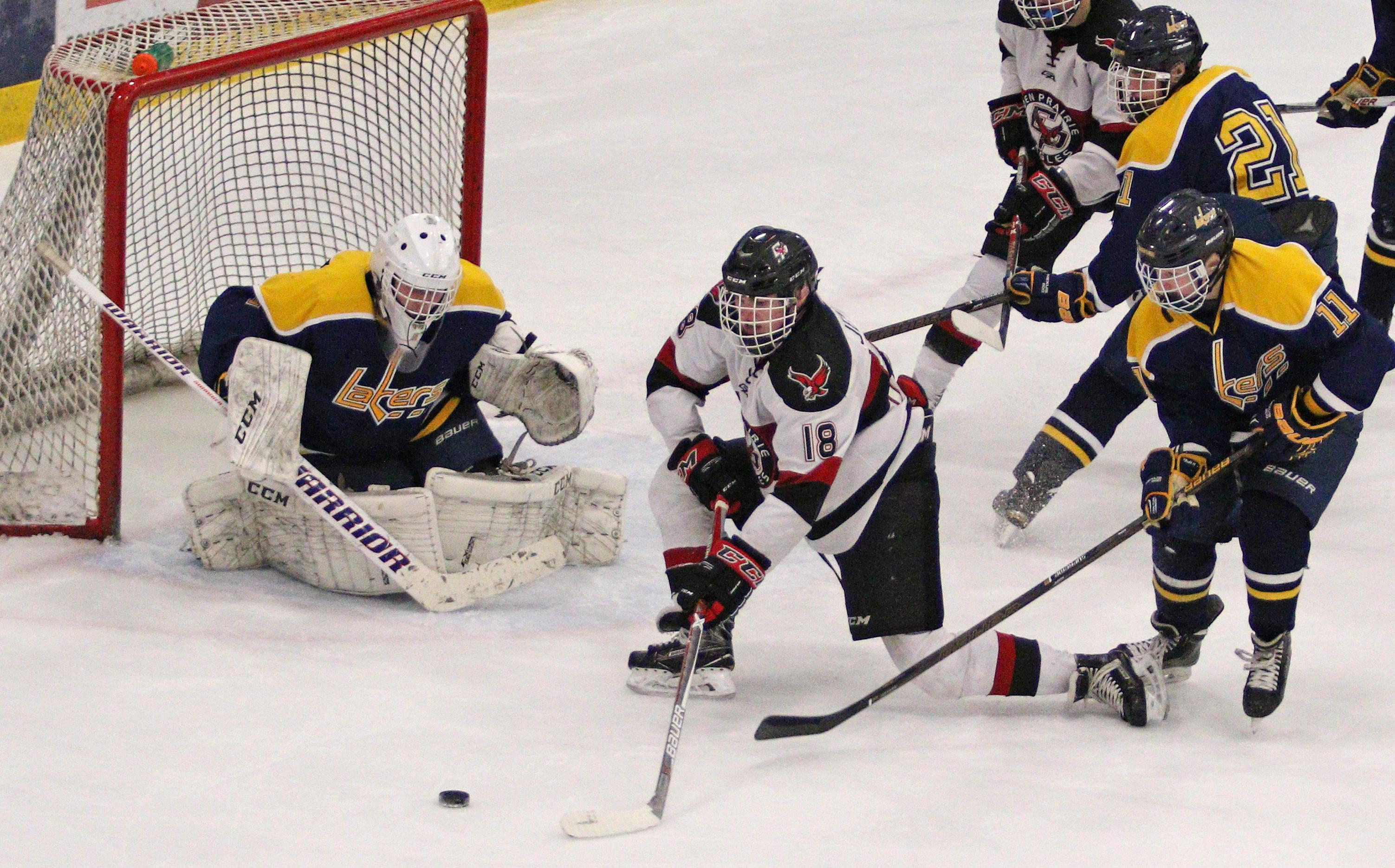 Sophomore forward Jack Jensen (18) puts pressure on Prior Lake goalie Danny Long.  Jensen would score one minute into the third period for the tying goal and shift momentum in Eden Prairie's favor.  Photo by Cheryl Myers, SportsEngine