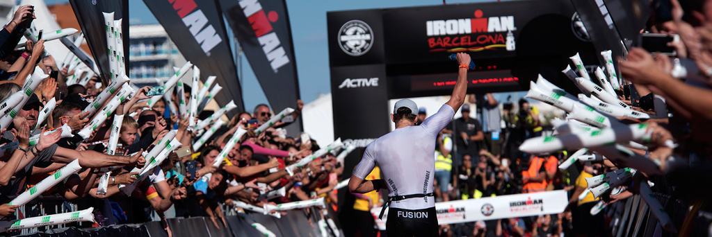 IRONMAN Barcelona athlete at the finish line with massive crowds cheering him up