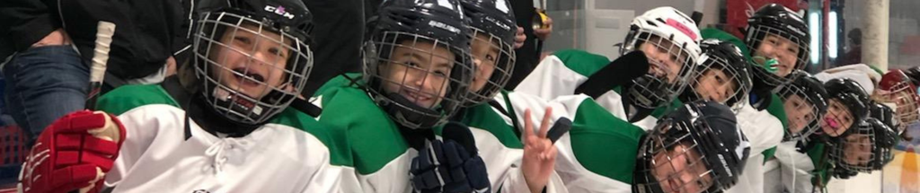 U10 Black hockey team smiling from the bench at a tournament