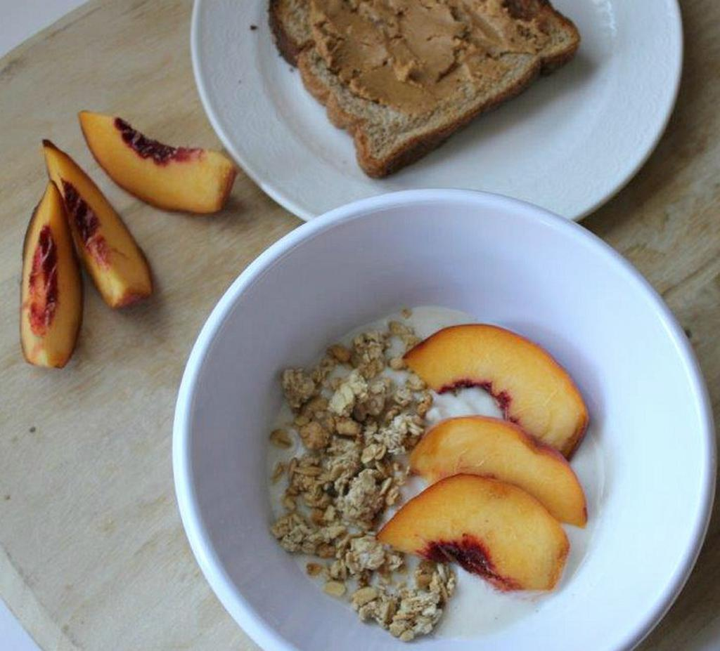 A breakfast of oatmeal, dried fruit, and a piece of toast with peanut butter