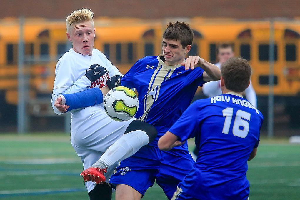 Holy Angels' Max Molldrem (4) battled for the ball with Austin's Igor Blinkow. Photo by Mark Hvidsten, SportsEngine