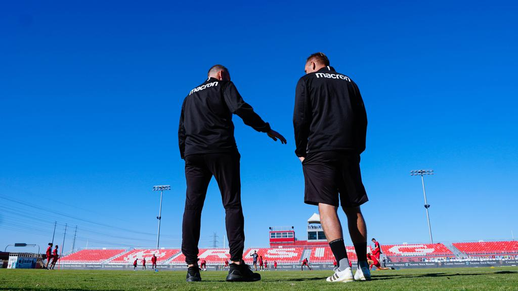 A look at coaches Steve Cooke and Rick Schantz stand together from behind with their backs to the camera as they look out to the Casino Arizona Field stadium