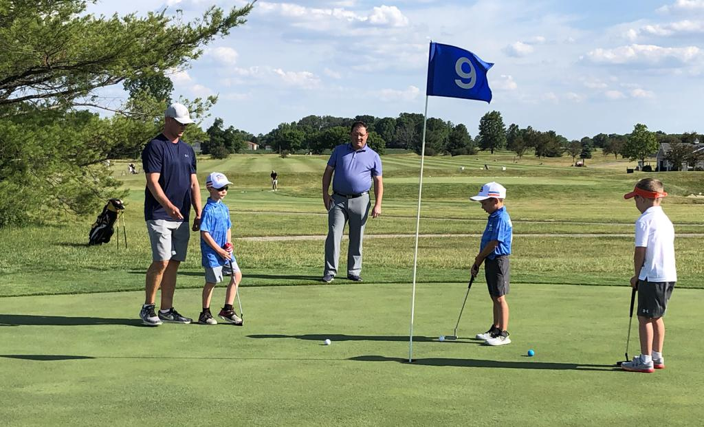 PGA Jr. League players putt while parents look on