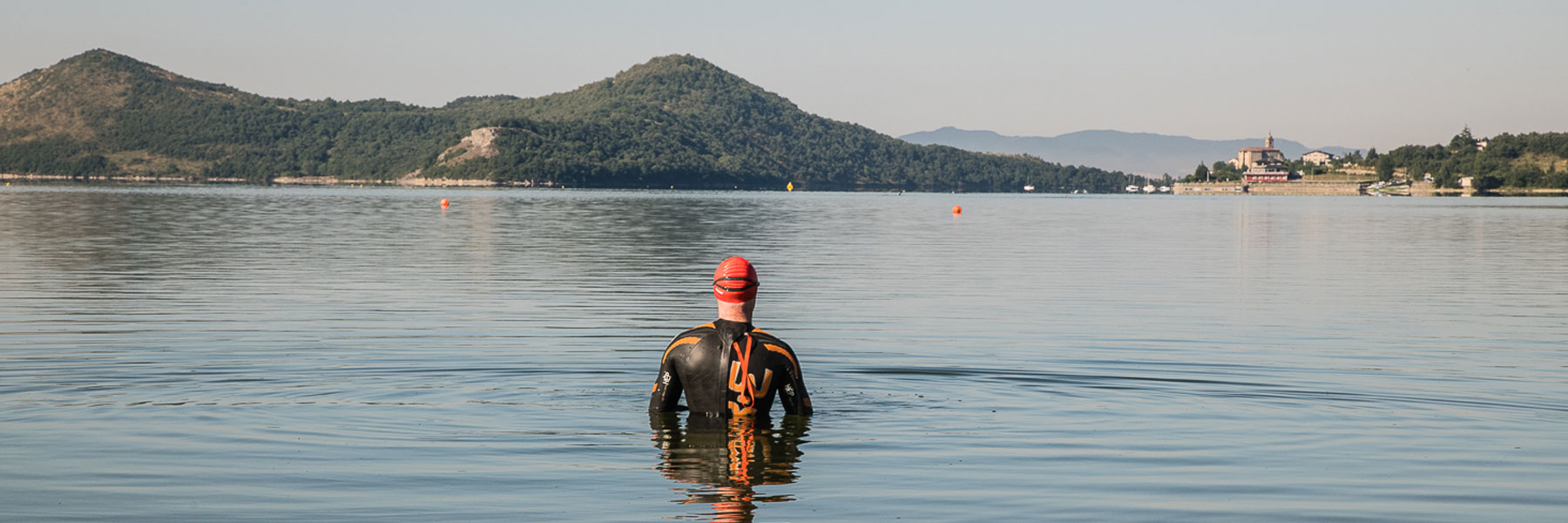 IRONMAN Vitoria-Gasteiz athlete standing in Ulibarri-Gamboa lake located in the Landa Provincial Park who is looking around and ready for the swim