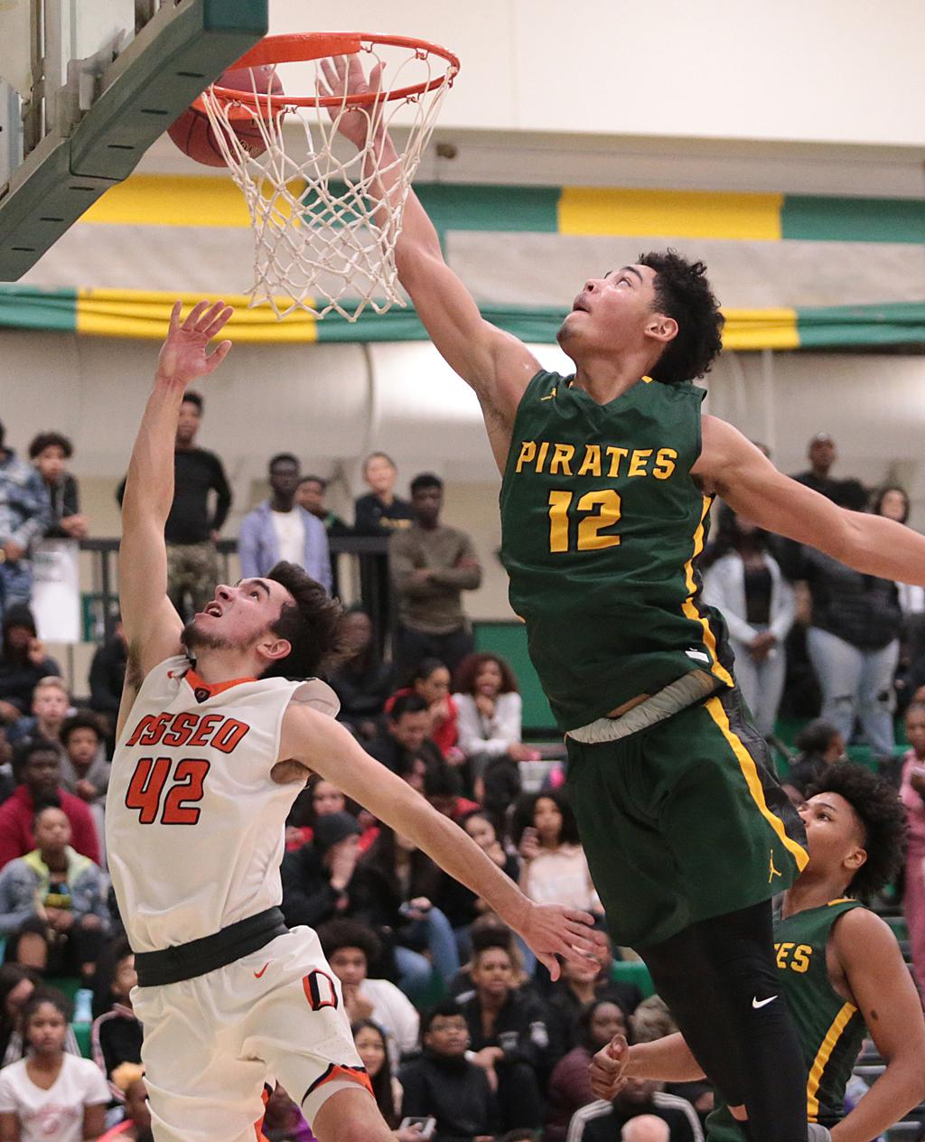 Tommy Chatman (12) reaches for the block on a lay up attempt from Zach Theisen (42). Chatman threw down 14 points for the Pirates as they hand the Orioles a 72-58 loss in the Northwest Suburban matchup. Photo by Cheryl Myers, SportsEngine
